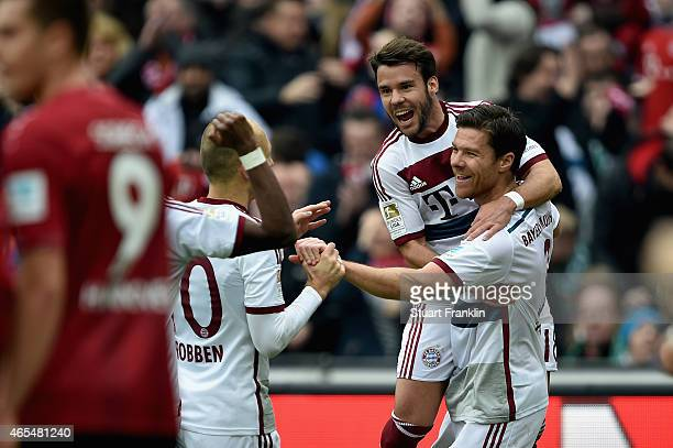 Xabi Alonso of FC Bayern Muenchen celebrates with team mates Juan Bernat and Arjen Robben as he scores their first goal during the Bundesliga match...