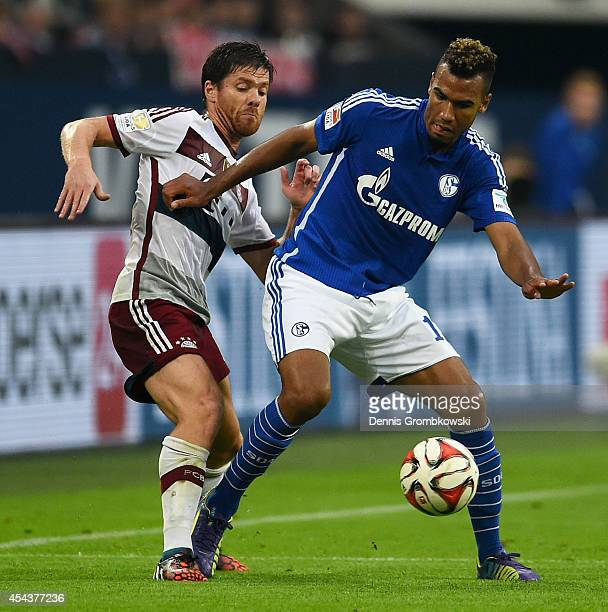 Xabi Alonso of FC Bayern Muenchen challenges Eric Maxim ChoupoMoting of FC Schalke 04 during the Bundesliga match between FC Schalke 04 and FC Bayern...