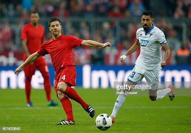 Xabi Alonso of FC Bayern Muenchen is challenged by Kerem Demirbay of TSG Hoffenheim during the Bundesliga match between Bayern Muenchen and TSG 1899...