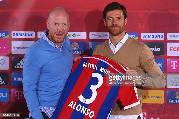 Xabi Alonso of FC Bayern Muenchen poses with Matthias Sammer sporting director of FC Bayern Muenchen during a press conference at Bayern Muenchen's...