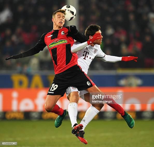 Xabi Alonso of Muechen challenges Janik Haberer of Freiburg during the Bundesliga match between SC Freiburg and Bayern Muenchen at SchwarzwaldStadion...