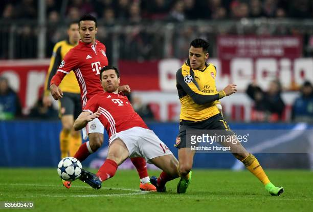 Xabi Alonso of Muenchen and Alexis Sanchez of Arsenal battle for the ball during the UEFA Champions League Round of 16 first leg match between FC...
