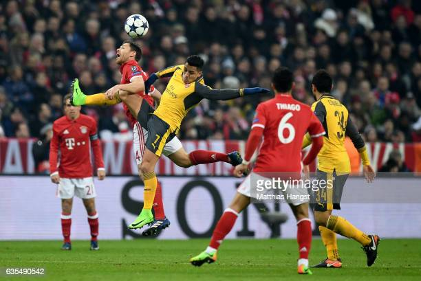 Xabi Alonso of Muenchen and Alexis Sanchez of Arsenal jump to head for the ball during the UEFA Champions League Round of 16 first leg match between...