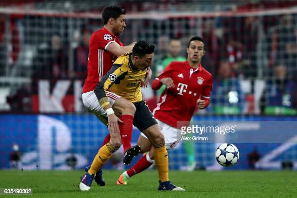 Xabi Alonso of Muenchen and Mesut Oezil of Arsenal battle for the ball during the UEFA Champions League Round of 16 first leg match between FC Bayern...