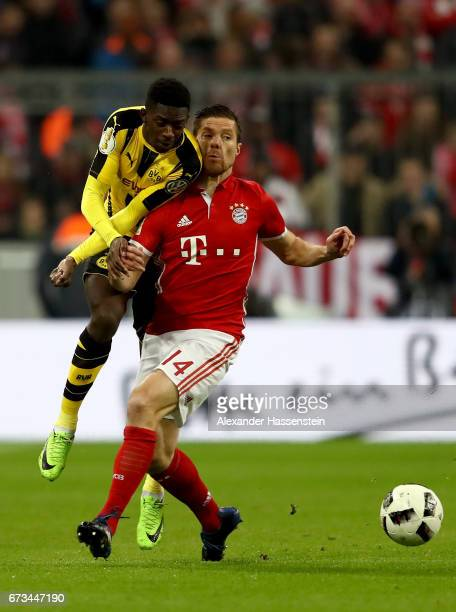 Xabi Alonso of Muenchen and Ousmane Dembele of Dortmund battle for the ball during the DFB Cup semi final match between FC Bayern Muenchen and...