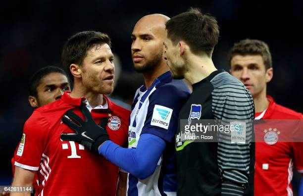 Xabi Alonso of Muenchen argues with Rune Jarstein goalkeeper of Berlin during the Bundesliga match between Hertha BSC and Bayern Muenchen at...