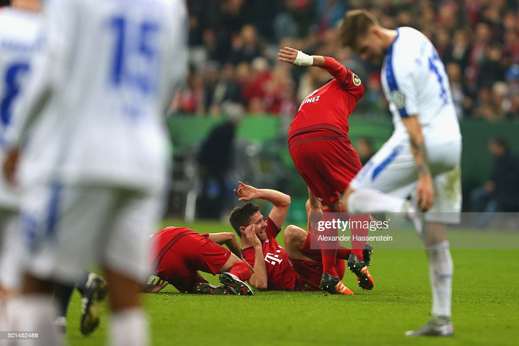 Xabi Alonso of Muenchen celebrates scoring the opening goal with his team mates during the round of 16 DFB Cup match between FC Bayern Muenchen and...