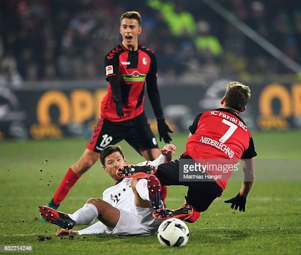 Xabi Alonso of Muenchen challenges Florian Niederlechner of Freiburg during the Bundesliga match between SC Freiburg and Bayern Muenchen at...