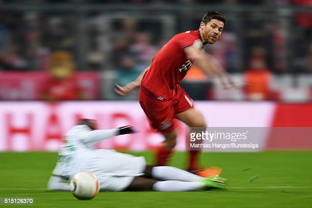 Xabi Alonso of Muenchen is challenged by Anthony Ujah of Bremen during the Bundesliga match between FC Bayern Muenchen and Werder Bremen at Allianz...