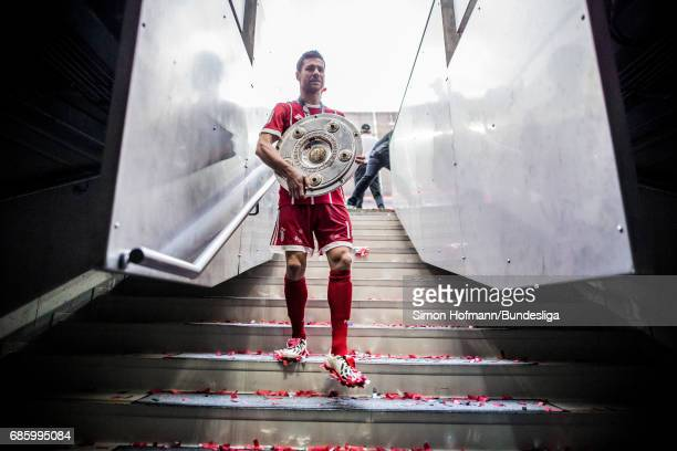 Xabi Alonso of Muenchen leaves the pitch with the trophy after the Bundesliga match between Bayern Muenchen and SC Freiburg at Allianz Arena on May...