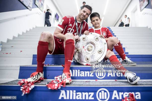 Xabi Alonso of Muenchen poses with the trophy in the player's tunnel after the Bundesliga match between Bayern Muenchen and SC Freiburg at Allianz...