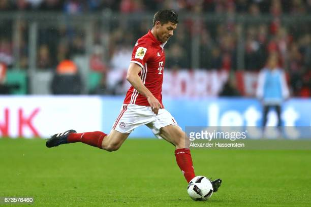 Xabi Alonso of Muenchen runs with the ball during the DFB Cup semi final match between FC Bayern Muenchen and Borussia Dortmund at Allianz Arena on...