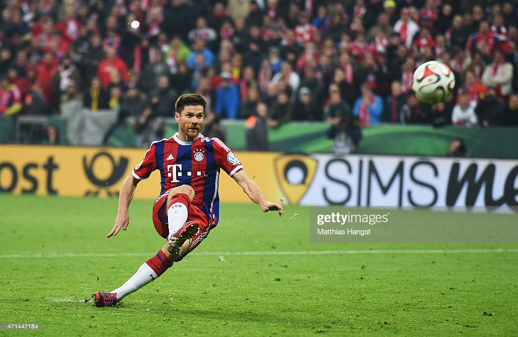 Xabi Alonso of Muenchen slips over during the penalty shoot out during the DFB Cup semi final match between FC Bayern Muenchen and Borussia Dortmund...