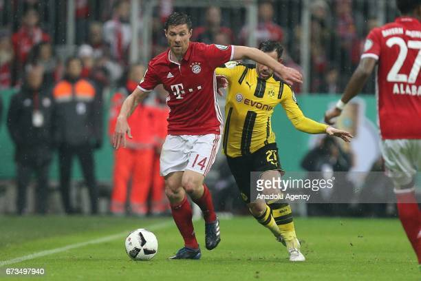 Xabi Alonso of Munich and Gonzalo Castro of Dortmund vie for the ball during the German Cup semi final soccer match between FC Bayern Munich and...
