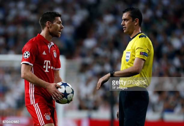 Xabi Alonso of Munich speak with Viktor Kassai during the UEFA Champions League Quarter Final second leg match between Real Madrid CF and FC Bayern...