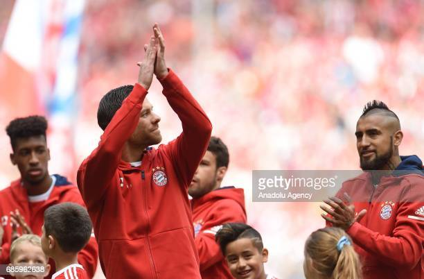 Xabi Alonso of Munich stands in between his teammates Kingsley Coman and Arturo Vidal and waves during his farewell ceremony prior to the Bundesliga...