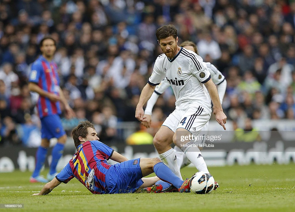 Xabi Alonso (R) of Real Madrid and MIguel Herrero of Levante compete for the ball during the La Liga match between Real Madrid and Levante at Estadio Santiago Bernabeu on April 6, 2013 in Madrid, Spain.