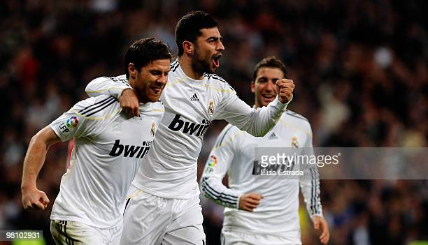 Xabi Alonso of Real Madrid celebrates with Raul Albiol after scoring during the La Liga match between Real Madrid and Atletico de Madrid at Estadio...