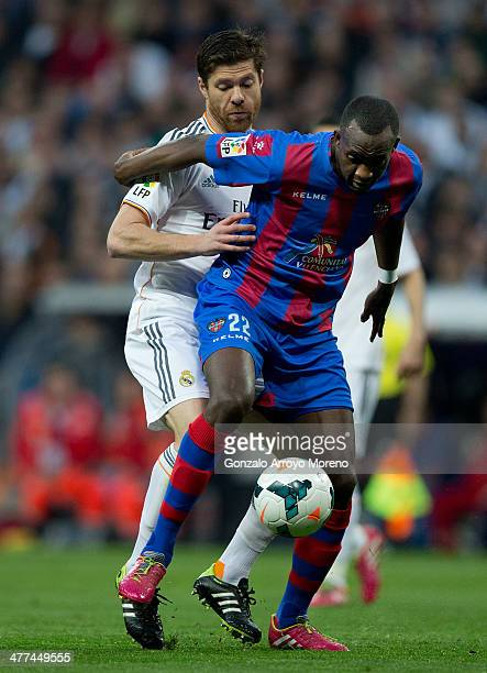 Xabi Alonso of Real Madrid CF competes for the ball behind Mohamed Sissoko of Levante UD during the La Liga match between Real Madrid CF and Levante...