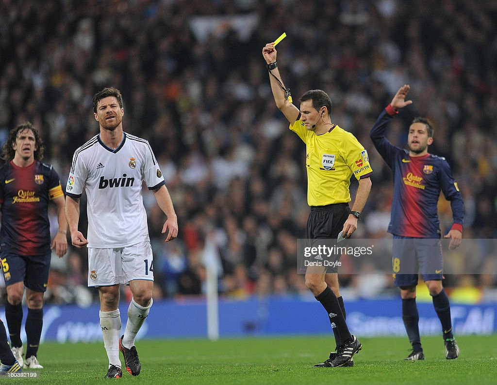 Xabi Alonso (L) of Real Madrid CF is booked by referee Clos Gomez during the Copa del Rey semi final, first leg match between Real Madrid CF and FC Barcelona at Estadio Santiago Bernabeu on January 30, 2013 in Madrid, Spain.