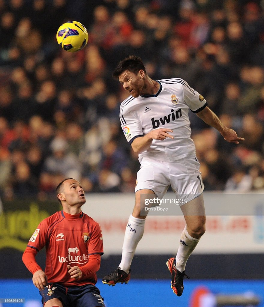 Xabi Alonso (R) of Real Madrid gets to the ball ahead of Juan Martinez 'Nino' of Osasuna during the La Liga match between Osasuna and Real Madrid at estadio Reino de Navarra on January 12, 2013 in Pamplona, Spain.