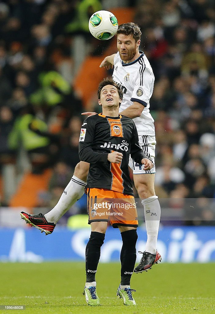 Xabi Alonso of Real Madrid heads the ball aginst Pablo Piatti of Valencia during the Copa del Rey quarter-final, first leg match between Real Madrid and Valencia at Estadio Santiago Bernabeu on January 15, 2013 in Madrid, Spain.