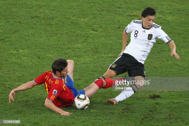 Xabi Alonso of Spain and Mesut Oezil of Germany battle for the ball during the 2010 FIFA World Cup South Africa Semi Final match between Germany and...