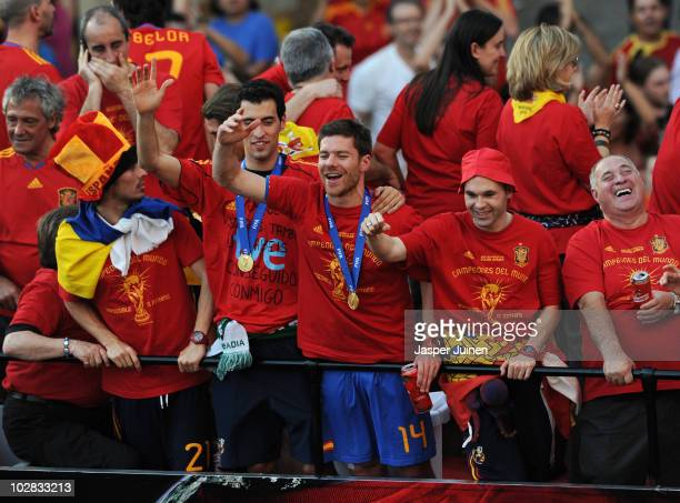 Xabi Alonso of Spain celebrates with his teammates Andres Iniesta and Raul Albiol during the Spanish team's victory parade following their victory in...