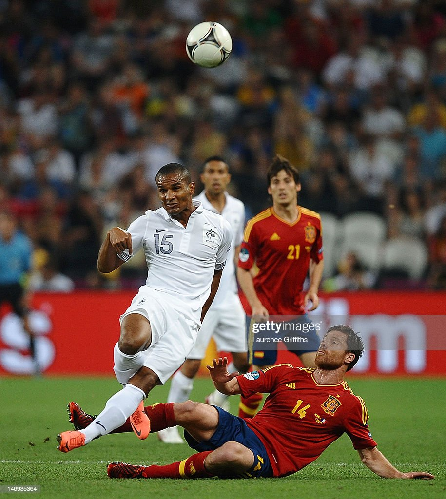 Xabi Alonso of Spain challenges Florent Malouda of France during the UEFA EURO 2012 quarter final match between Spain and France at Donbass Arena on June 23, 2012 in Donetsk, Ukraine.