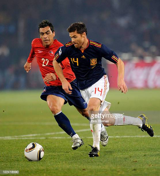 Xabi Alonso of Spain dribbles past Esteban Paredes of Chile during the 2010 FIFA World Cup South Africa Group H match between Chile and Spain at...