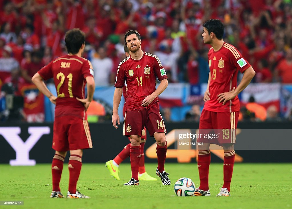 Xabi Alonso of Spain looks on as his teammates wait to kickoff after allowing Chile's second goal during the 2014 FIFA World Cup Brazil Group B match...