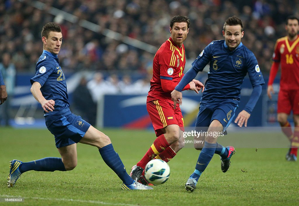 Xabi Alonso of Spain passes the ball between Laurent Koscielny and Yohan Cabaye of France during the FIFA World Cup 2014 qualifier match between France and Spain at the Stade de France on March 26, 2013 in Saint-Denis near Paris, France.