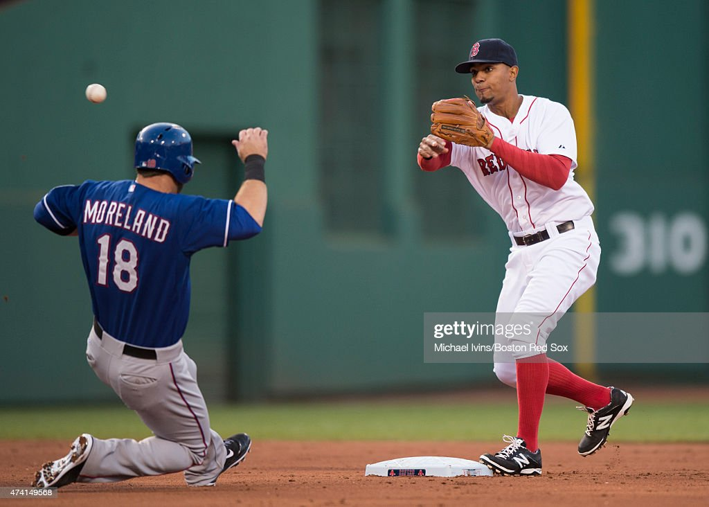 Xander Bogaerts #2 of the Boston Red Sox attempts to complete a double play over the head of Mitch Moreland #18 of the Texas Rangers during the second inning at Fenway Park in Boston, Massachusetts on May 20, 2015.