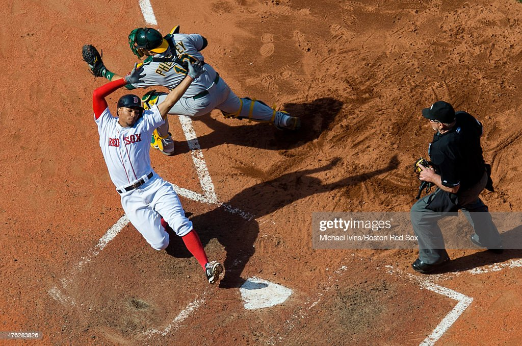 Xander Bogaerts #2 of the Boston Red Sox avoids the tag of Josh Phegley #19 of the Oakland Athletics to score a run during the eighth inning at Fenway Park in Boston, Massachusetts on June 7, 2015.