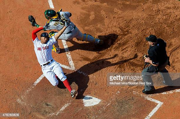 Xander Bogaerts of the Boston Red Sox avoids the tag of Josh Phegley of the Oakland Athletics to score a run during the eighth inning at Fenway Park...