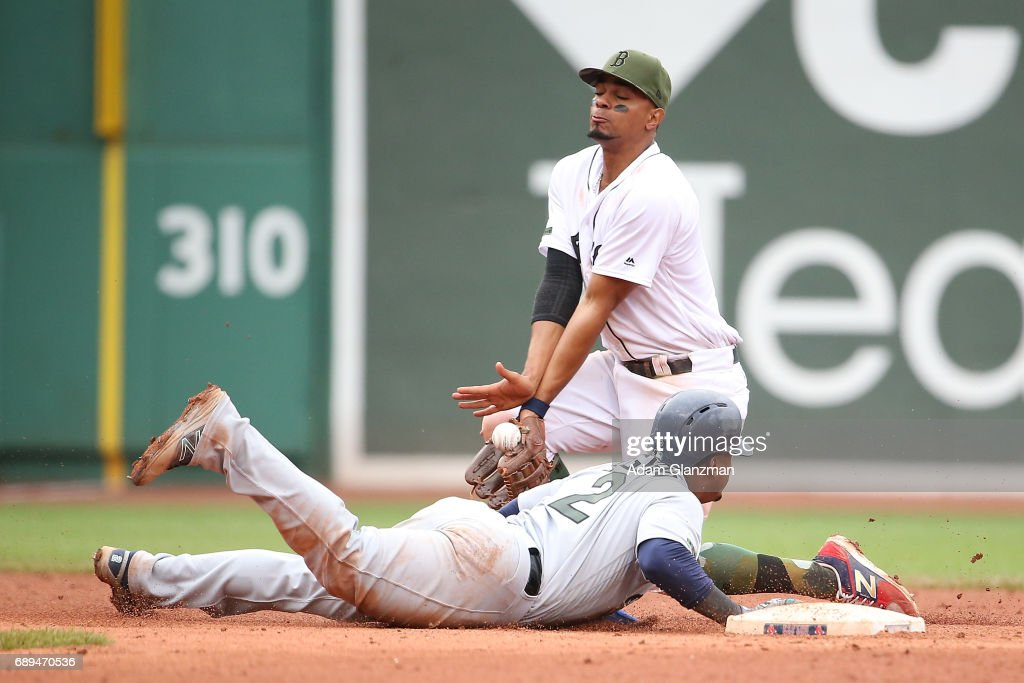 Xander Bogaerts #2 of the Boston Red Sox bobbles the ball as Jean Segura #2 of the Seattle Mariners slides back ito second base in the ninth inning of a game at Fenway Park on May 28, 2017 in Boston, Massachusetts.