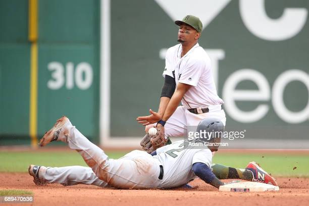 Xander Bogaerts of the Boston Red Sox bobbles the ball as Jean Segura of the Seattle Mariners slides back ito second base in the ninth inning of a...