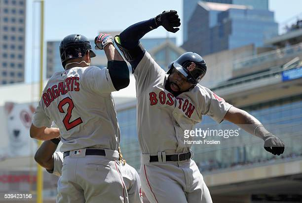 Xander Bogaerts of the Boston Red Sox congratulates teammate Jackie Bradley Jr #25 on hitting a threerun home run against the Minnesota Twins during...
