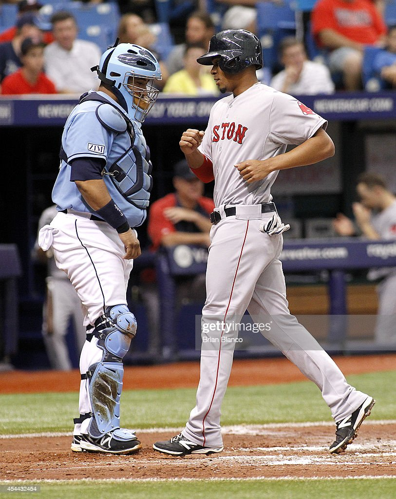 Xander Bogaerts #2 of the Boston Red Sox crosses home plate ahead of catcher Jose Molina #28 of the Tampa Bay Rays to score off of a single by Christian Vazquez during the third inning of a game on August 31, 2014 at Tropicana Field in St. Petersburg, Florida.