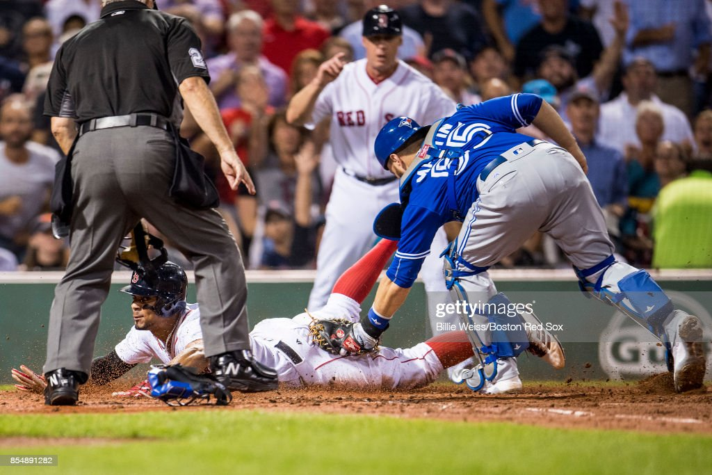 Xander Bogaerts #2 of the Boston Red Sox evades the tag of Russell Martin #55 of the Toronto Blue Jays as he scores during the second inning of a game on September 27, 2017 at Fenway Park in Boston, Massachusetts.