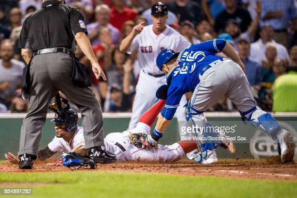 Xander Bogaerts of the Boston Red Sox evades the tag of Russell Martin of the Toronto Blue Jays as he scores during the second inning of a game on...