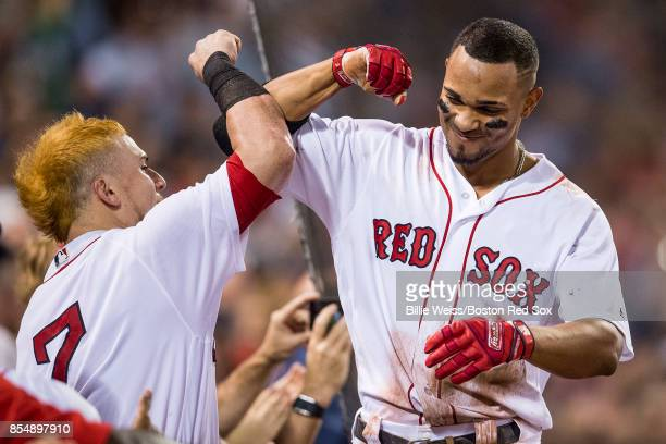 Xander Bogaerts of the Boston Red Sox high fives Christian Vazquez after hitting a three run home run during the third inning of a game against the...
