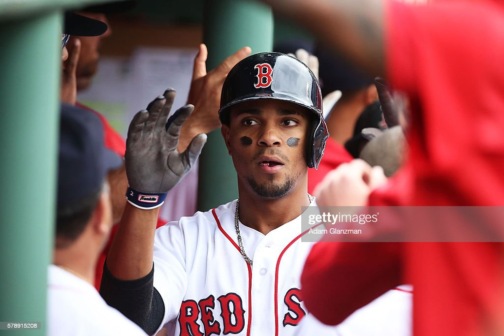 Xander Bogaerts of the Boston Red Sox high fives his teammates after hitting a tworun home run in the fourth inning of the game against the Tampa Bay...