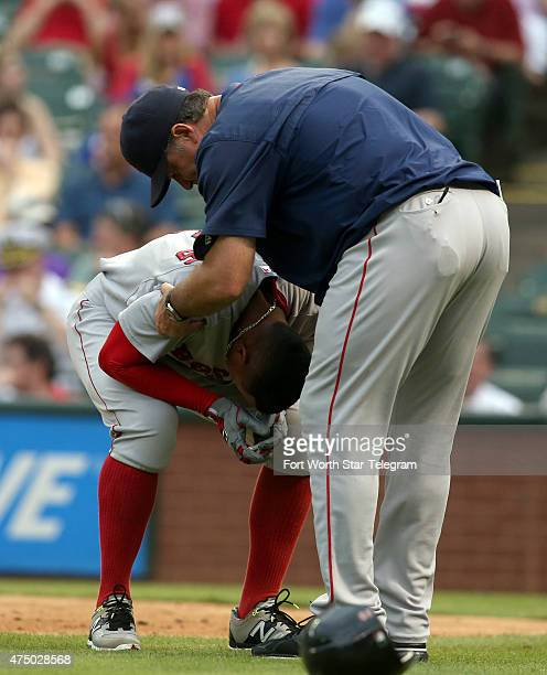 Xander Bogaerts of the Boston Red Sox is checked on by manager John Farrell right after being hit by a pitch in the second inning against the Texas...