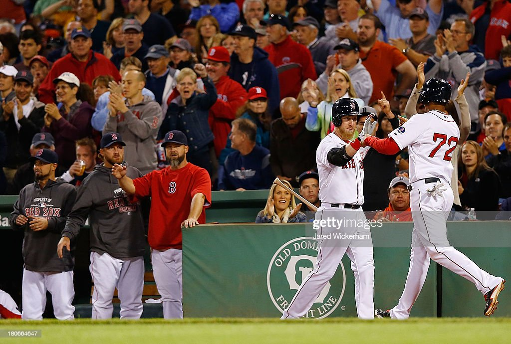 Xander Bogaerts #72 of the Boston Red Sox is congratulated by teammate Mike Carp #37 of the Boston Red Sox after scoring against the New York Yankees during the game on September 15, 2013 at Fenway Park in Boston, Massachusetts.