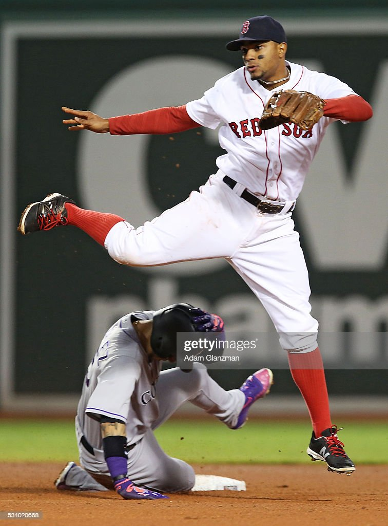 Xander Bogaerts #2 of the Boston Red Sox leaps over Carlos Gonzalez #5 of the colorado Rockies as he turns a double play in the fourth inning of a game at Fenway Park in Boston, Massachusetts on May 24, 2016.