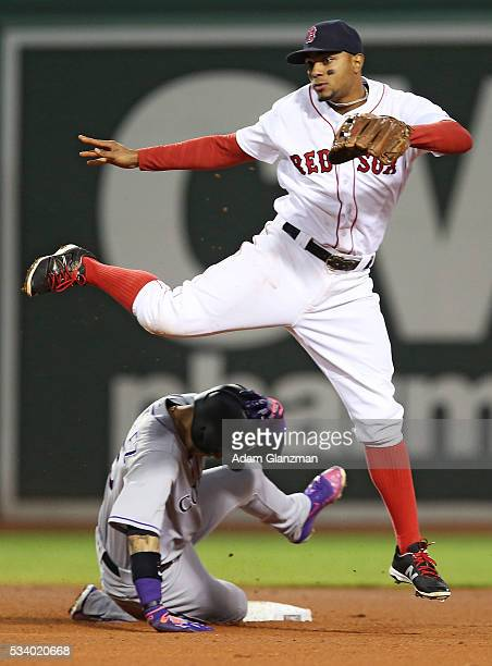 Xander Bogaerts of the Boston Red Sox leaps over Carlos Gonzalez of the colorado Rockies as he turns a double play in the fourth inning of a game at...