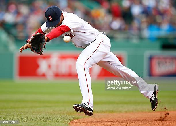 Xander Bogaerts of the Boston Red Sox misses a ground ball in the infield against the Toronto Blue Jays during the game at Fenway Park on May 22 2014...