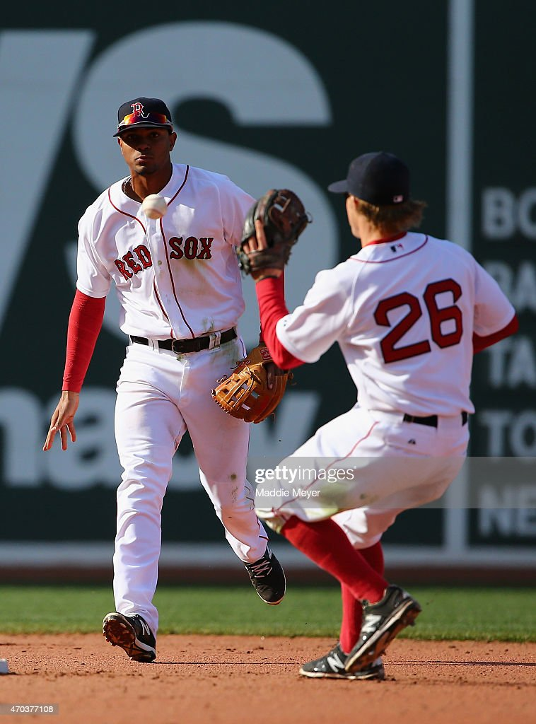 Xander Bogaerts #2 of the Boston Red Sox passes the ball off to Brock Holt #26 in a double play against the Baltimore Orioles during the ninth inning at Fenway Park on April 19, 2015 in Boston, Massachusetts. The Orioles defeat the Red Sox 8-3.