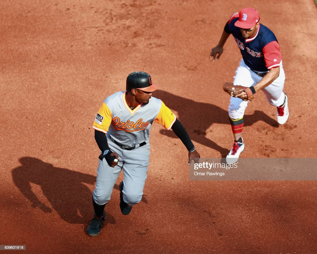 Xander Bogaerts #2 of the Boston Red Sox runs out Adam Jones #10 of the Baltimore Orioles at the top of the second inning during the game at Fenway Park on August 26, 2017 in Boston, Massachusetts.